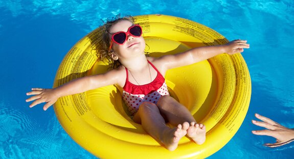 Girl with Sunglasses in Pool Float enjoying a day in the pool.