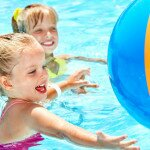 little girls playing in swimming pool with beach ball