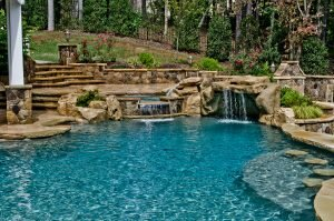 Pool and spa with stone accents and water features